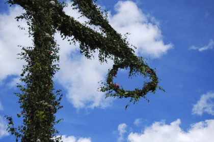Detail of midsummer pole at blue sky with white clouds