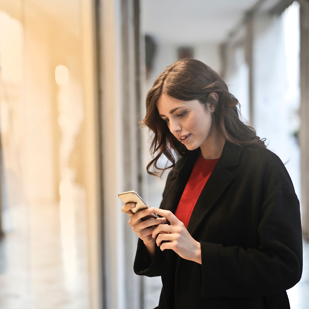 close-up-photo-of-mystery shopper in-black-coat-using-smartphone 1024 px
